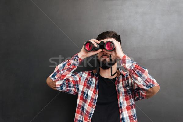 Jóképű férfi kockás póló áll néz látcső Stock fotó © deandrobot