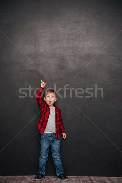 Shocked little boy standing over chalkboard and pointing up Stock photo © deandrobot