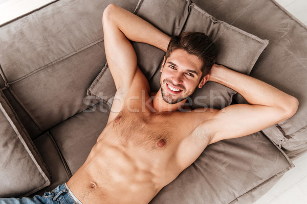 Top view of smiling relaxed young man lying on sofa Stock photo © deandrobot