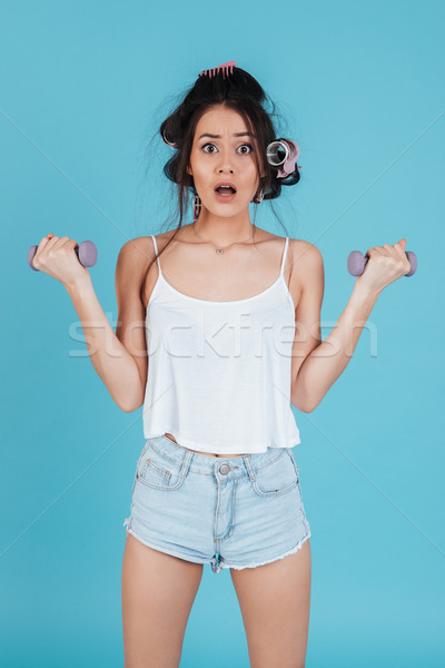 Surprised woman with curlers holding weights and looking at camera Stock photo © deandrobot