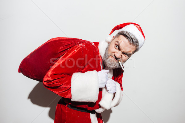 Angry man santa claus smoking and holding gift sack Stock photo © deandrobot