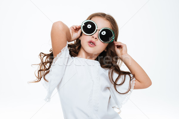 Cute amusing little girl posing in stylish round sunglasses Stock photo © deandrobot