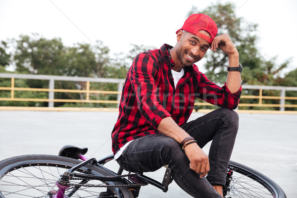 Happy dark skinned boy sitting on his bicycle Stock photo © deandrobot