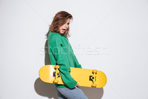 Attractive skater woman with skateboard. Stock photo © deandrobot