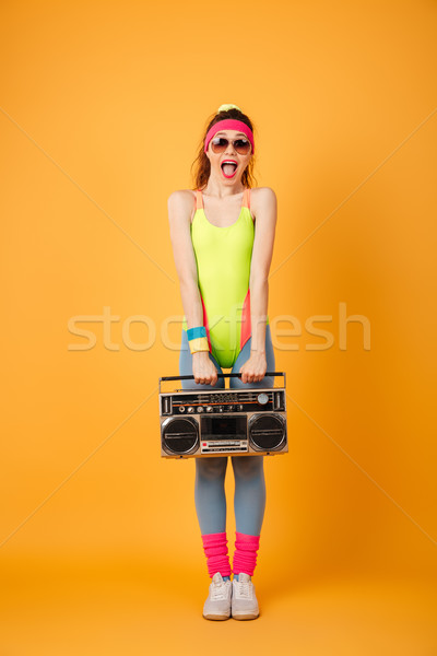 Happy excited young woman athlete holding retro boombox and shouting Stock photo © deandrobot