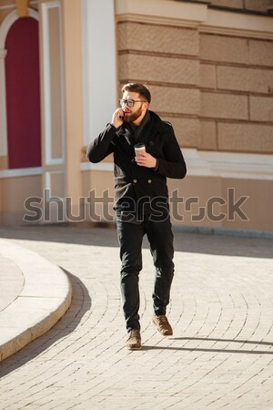 Happy man using cell phone and drinking coffee in city Stock photo © deandrobot