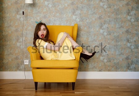 Portrait of a smiling pretty pin up woman leaning on chair Stock photo © deandrobot