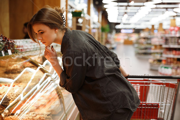 Concentrated young lady in supermarket choosing pastries. Stock photo © deandrobot