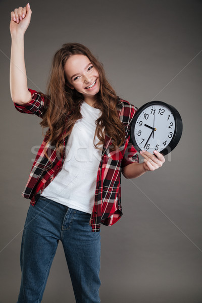 Happy young lady holding clock. Looking at camera. Stock photo © deandrobot