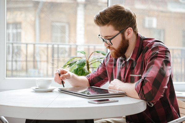 Handsome bearded young man using tablet computer. Stock photo © deandrobot