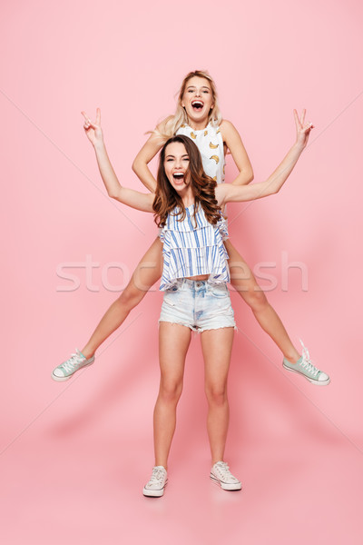 Two happy women standing isolated over pink background. Stock photo © deandrobot