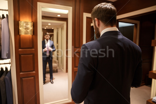 Stock photo: Image of man standing against mirror