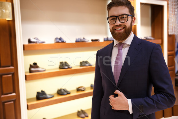 Happy man in suit and glasses stading near shelf Stock photo © deandrobot