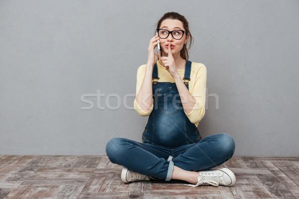 Zwangere vrouw praten mobiele telefoon stilte gebaar Stockfoto © deandrobot