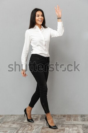 Happy charming young woman pointing and holding copyspace on palm Stock photo © deandrobot