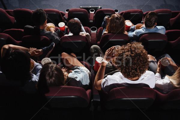 Friends sitting in cinema watch film eating popcorn Stock photo © deandrobot