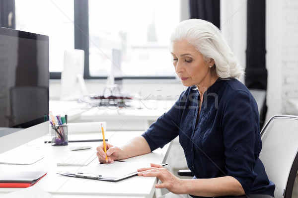 Mature business woman making notes on a piece of paper Stock photo © deandrobot