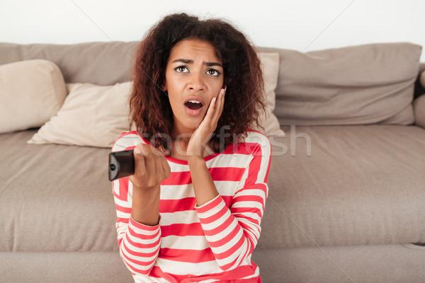 Megrémült nő ül távirányító kanapé afrikai Stock fotó © deandrobot