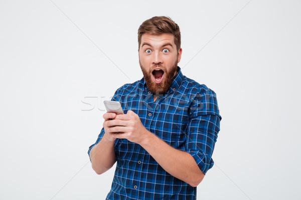 étonné barbu homme à carreaux shirt smartphone Photo stock © deandrobot