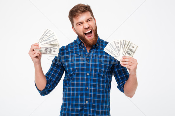 So happy bearded man in shirt holding money in hands Stock photo © deandrobot