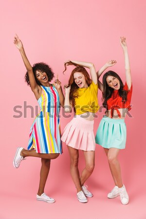 Happy women friends standing over yellow wall Stock photo © deandrobot