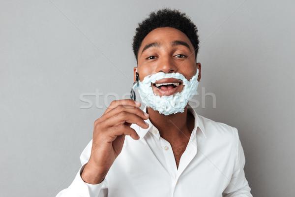 Fiatal afrikai férfi póló borotva közelkép Stock fotó © deandrobot