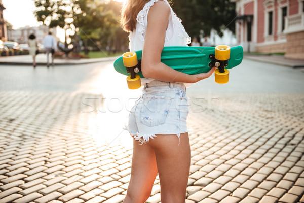 Kép fiatal nő gördeszka sétál kint nő Stock fotó © deandrobot