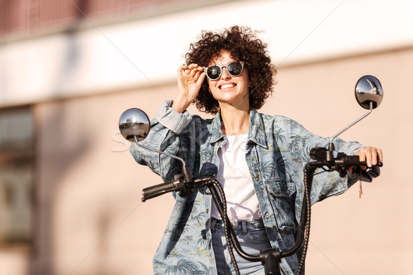 Image of pleased curly woman in sunglasses sitting on motorbike Stock photo © deandrobot