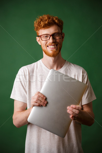 A portrait of young readhead bearded man in white tshirt holding Stock photo © deandrobot
