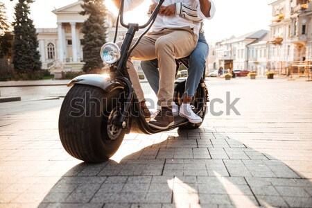 Full-length side view of young african couple rides on motorbike Stock photo © deandrobot