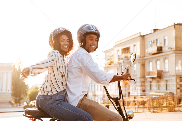 Side view of Carefree young african couple rides on motorbike Stock photo © deandrobot