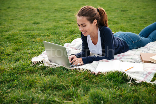 Portrait of a smiling beautiful student girl doing homework Stock photo © deandrobot