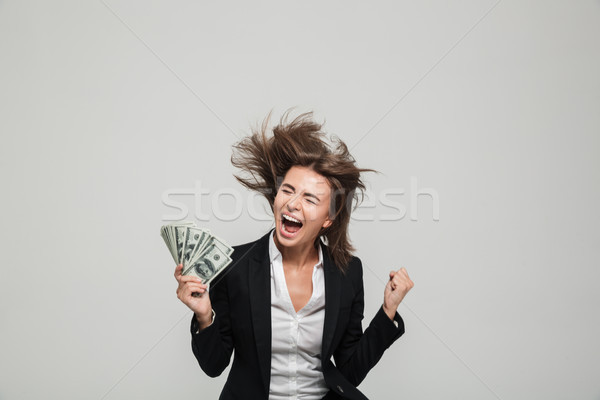 Portrait of a happy thrilled businesswoman in suit Stock photo © deandrobot
