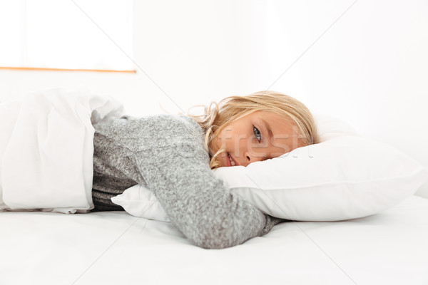 Portrait of a cute little girl hugging pillow while Stock photo © deandrobot