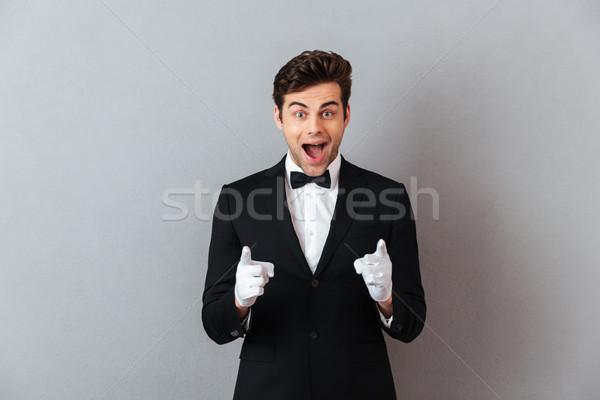 удивленный счастливым молодые официант указывая изображение Сток-фото © deandrobot