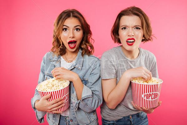 Shocked women friends eating popcorn watch film. Stock photo © deandrobot