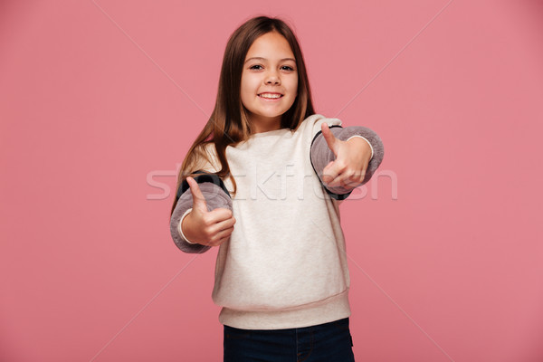 Happy brunette girl showing thumbs up and smiling to camera isolated Stock photo © deandrobot