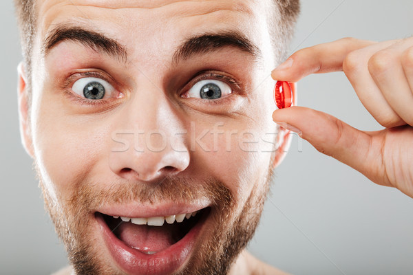 Close up portrait of a happy man holding red capsule Stock photo © deandrobot