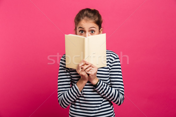 Shocked teenage girl covering face with book. Stock photo © deandrobot