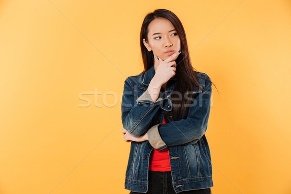 Pensive asian woman in jacket holding chin and looking away Stock photo © deandrobot