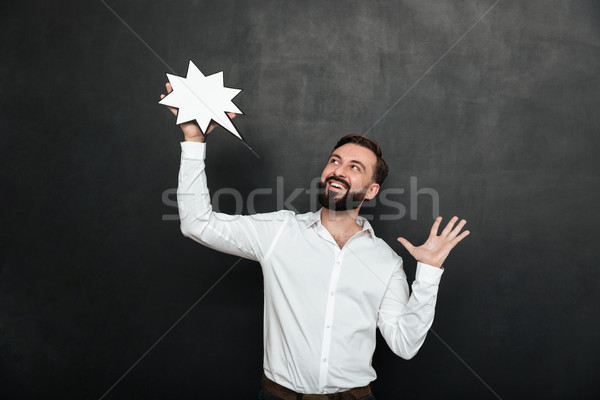 Photo of delighted man holding blank speech star and looking asi Stock photo © deandrobot