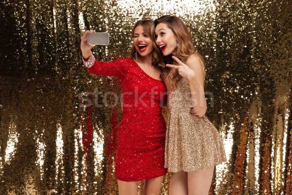 Portrait of two pretty happy women in sparkly dresses Stock photo © deandrobot