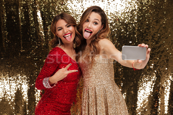 Portrait of two cheerful pretty women in sparkly dresses Stock photo © deandrobot