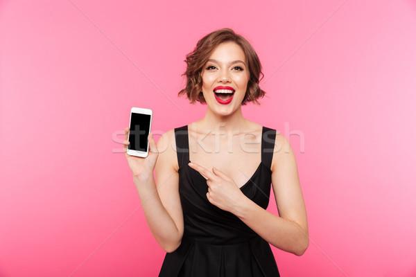 Portré boldog lány fekete ruha mutat ujj képernyő Stock fotó © deandrobot