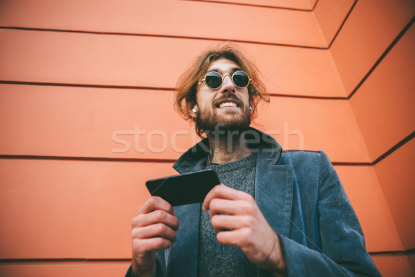 Portrait of a cheerful bearded man dressed in coat Stock photo © deandrobot