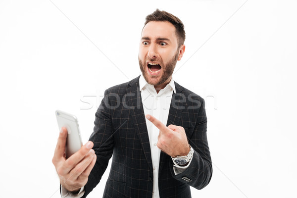 Portrait of an angry man holding mobile phone Stock photo © deandrobot