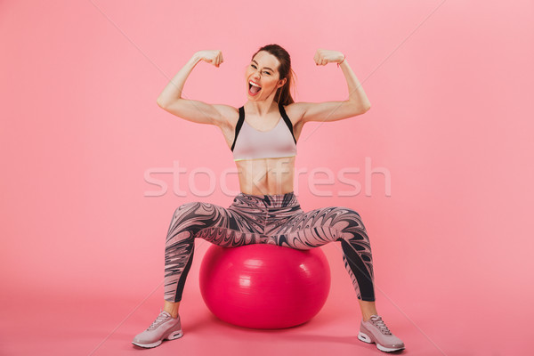 Full length image of happy sportswoman sitting on fitness ball Stock photo © deandrobot