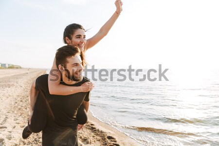 Happy young man carrying his girlfriend on his back Stock photo © deandrobot