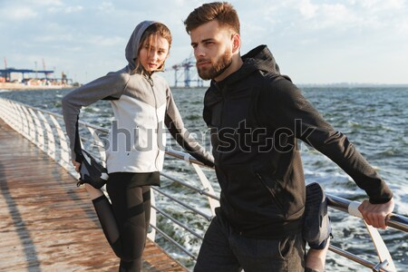 Confident young couple warming up before jogging Stock photo © deandrobot