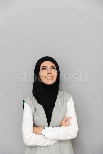 Image of muslim elegant woman 20s in hijab smiling and looking u Stock photo © deandrobot